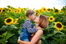 Woman Holding And Kiss Her Son Amidst Sunflower Field