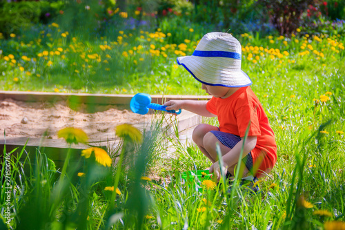 A boy with a bucket and a shovel playing in the sand Wallpaper Mural