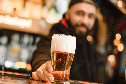 Photo Bearded and smiling barman gives beer