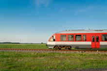 Fast Moving Train On Tracks Surrounded By Summer Meadows