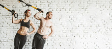 Athletic Man And Woman Doing TRX Workout.