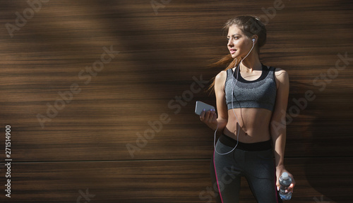 Sporty girl relaxing in shadow and listening to music Tablou Canvas