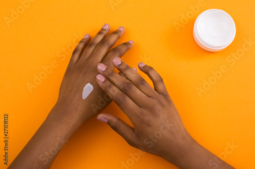 Tablou Canvas African american woman applying cosmetic hand cream on skin