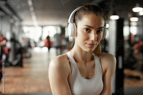 Close up portrait of young pretty european fitness woman at the gym and listen music in headphones. Breaking relax while exercise workout. Concept of health and sport lifestyle. Athletic Body.. - 271520576