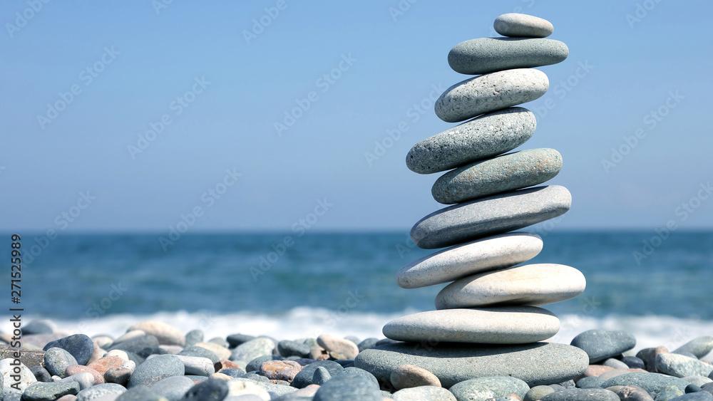 Fototapety, obrazy: folded pyramid of smooth stones on the seashore.