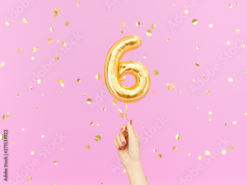 Obraz Six year birthday. Female hand holding Number 6 foil balloon. Six-year anniversary background. 3d rendering - fototapety do salonu
