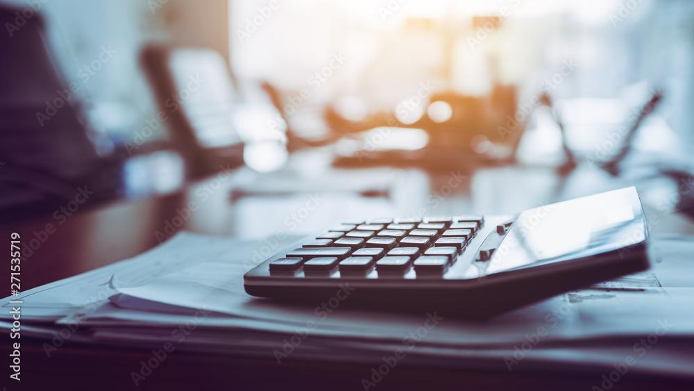 Fototapeta Close up calculator on business working desk, dark background.