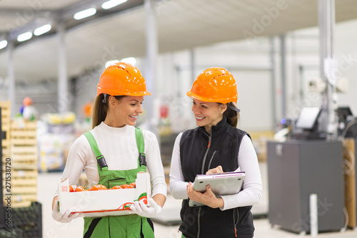 Positive female quality control inspector talking to a female employee at organic food production. - 271538720