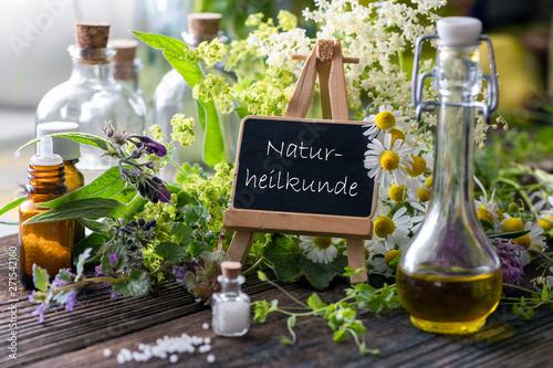 Schild mit Heilpflanzen und allerlei Fläschchen: Naturheilkunde