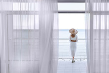 A Woman Enjoys The View Of The Sea With A Beautiful View From The Terrace In The Early Summer Morning.
