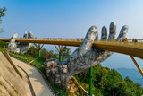 The Golden Bridge. The two giant colossal hands emerging from the mountains holding up the golden bridge at the height of 1,414 m from the sea level in Ba Na Hills. Vietnam.