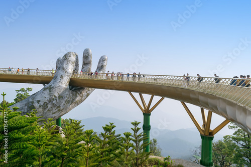Spoed Fotobehang Bruggen The Golden Bridge. The two giant colossal hands emerging from the mountains holding up the golden bridge at the height of 1,414 m from the sea level in Ba Na Hills. Vietnam.