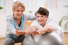 Female Physiotherapist Working Out With Senior Patient In Clinic