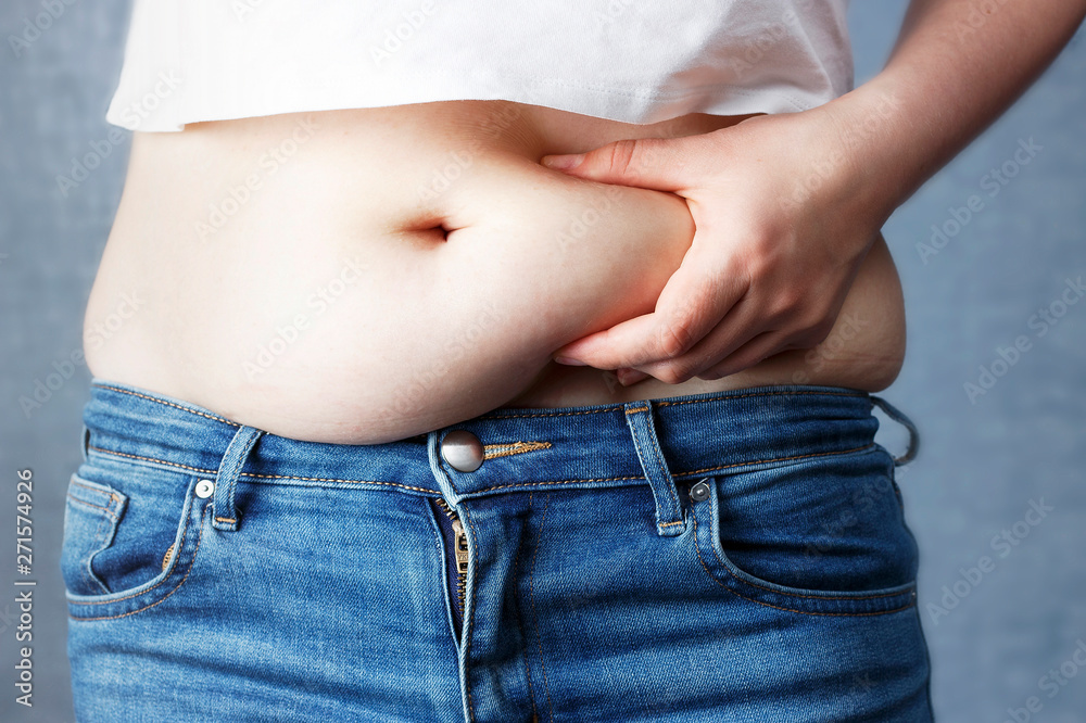 Fototapeta woman's hand holding excessive belly fat, overweight concept