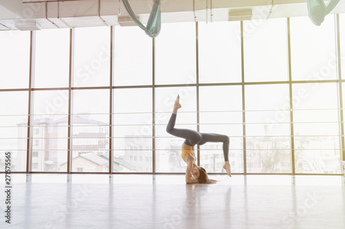 Poster Aeroport young attractive girl doing fitness exercises with yoga on the floor against the background of panoramic windows