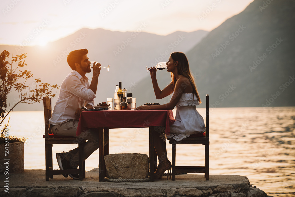 Fototapeta Couple is having a private event dinner on a tropical beach during sunset time