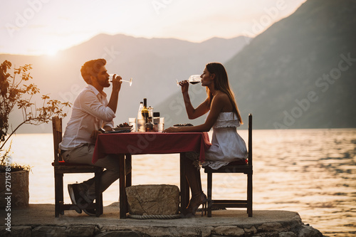 Fototapeta Couple is having a private event dinner on a tropical beach during sunset time obraz