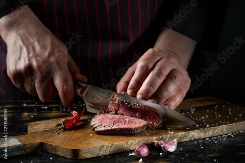 Obraz na płótnie Slicing juicy beef steak by knife in chef hands closeup