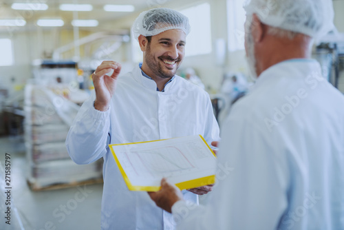 Photo  Young smiling food plant employee talking with his supervisor about quality of food