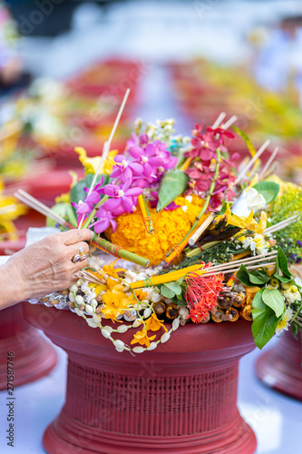 Photo Close up of hands with flowers and incense for illustration Buddhist tradition or Inthakin city pillar festival (Sai Khan Dok) in Chiang Mai, Thailand