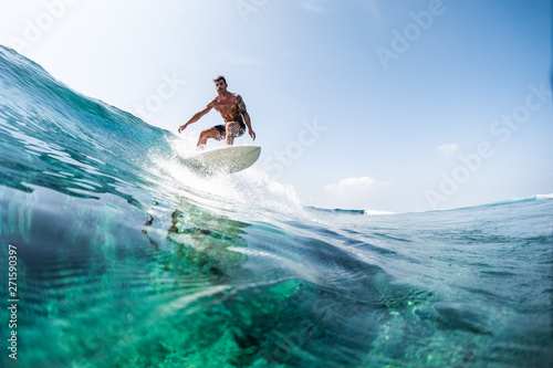Young man surfs the glassy ocean wave at sunny day Wallpaper Mural