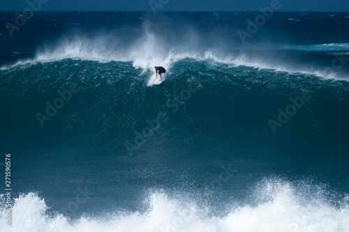 Surfer rides giant wave at the famous Banzai Pipeline surf spot located on the N Wallpaper Mural