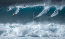 Four Surfers Share The Giant Wave At The Famous Waimea Bay Surf Spot Located On The North Shore Of Oahu In Hawaii