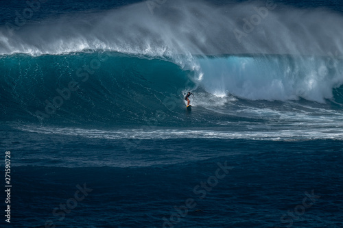 Stampa su Tela  Surfer rides furious wave at the famous Waimea Bay surf spot located on the Nort