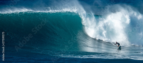 Surfer rides giant wave at the famous Waimea Bay surf spot located on the North Wallpaper Mural