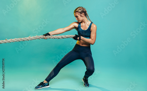 Fototapeta Tough sports woman exercising with battling rope obraz