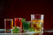 Alcoholic drink with ice and mint in a light smoke on the red background