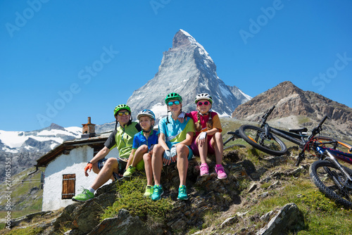 Fototapeta  Happy family riding a bike in a beautiful mountain landscape during vacation in the Swiss