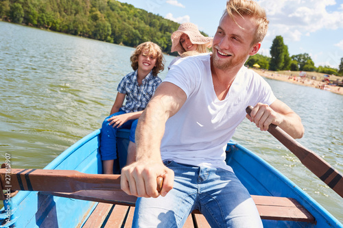 Happy father rows his family in the boat Canvas Print