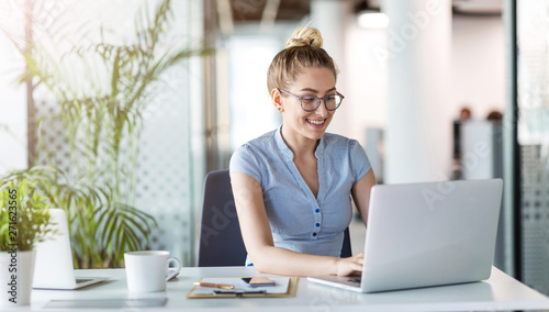 Fotografia  Young business woman working on laptop in office