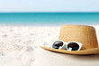 Hat and sunglasses on sand near sea, space for text. Stylish beach accessories