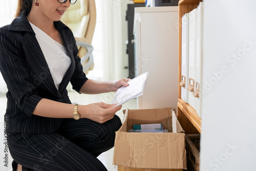 Poster Echelle de hauteur Asian young businesswoman sitting near the closet and packed documents into the box