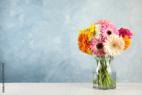 Fotografie, Obraz Bouquet of beautiful bright gerbera flowers in glass vase on table against color background
