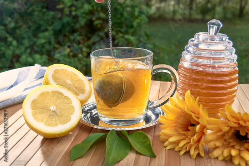 Tea filter ball falling into a glass of hot water. Tablou Canvas