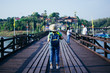 rear of woman travel and stand on wooden Mon bridge at Kanchanaburi. soft focus.