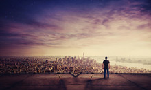Rear View Of Young Man Standing On The Rooftop Of A Skyscraper Watching Sunset Over The Big City Horizon. Businessman On The Roof Getting Inspired