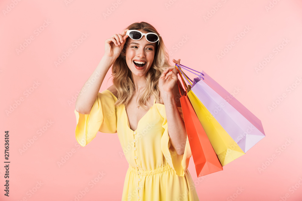 Fototapeta Beautiful happy young blonde woman posing isolated over pink wall background holding shopping bags.