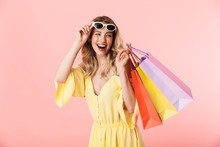 Beautiful Happy Young Blonde Woman Posing Isolated Over Pink Wall Background Holding Shopping Bags.
