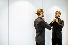 Handsome Man Wearing Black Shirt, Preparing For The Formal Event, While Standing Near The Mirror At The Wardrobe At Home