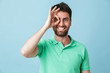 canvas print picture - Happy young handsome bearded man posing isolated over blue wall background looking camera showing okay gesture.