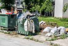 Big Pile Of Overflowing Garbage And Junk With Jacket And Clothes On The Dumpster Cans Pollution The City With Trash And Waste