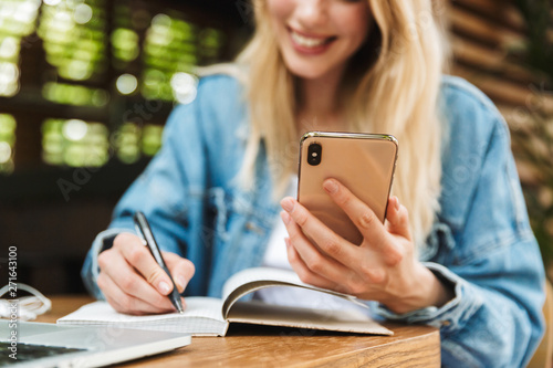 Photo  Happy young woman student posing outdoors in cafe using laptop computer writing notes in notebook