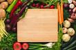 Leinwandbild Motiv Empty Wood Cutting Board Mockup with Fresh Vegetables. Vegetarian Raw Food. Healthy Eating Concept with Copy Space.