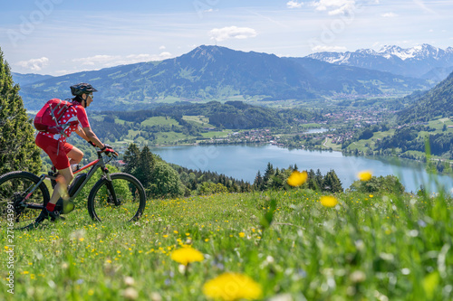 senior woman mountainbiking on a e-mountainbike in early spring, in the Allgaeu Wallpaper Mural