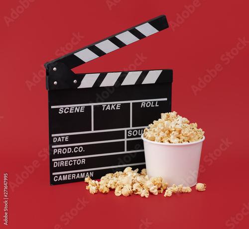 Vászonkép Clapper board with popcorn against red background,Cinema minimal concept