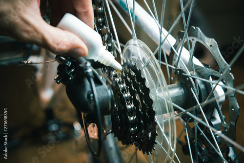 Pinturas sobre lienzo  Closeup of male hands cleaning and oiling a bicycle chain and gear with oil spray